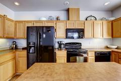 light brown kitchen with black appliances - stock photo