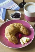 Croissant with butter on plate, jam and Cafe au lait - stock photo