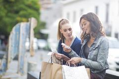 Two female friends looking at their shopping lists - stock photo