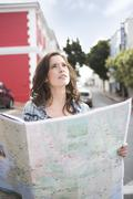 Young woman orientating with city map - stock photo