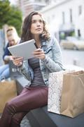 Young woman trying to orientate with her digital tablet - stock photo