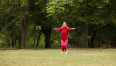 Young woman doing squats in park Stock Footage