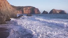 Sunset waves crash against cliffs Stock Footage