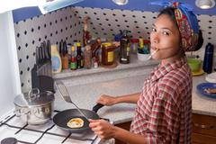 Asian woman with cigarette to cook in the kitchen - stock photo