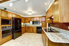 beautiful kitchen interior with granite tops and black appliances - stock photo