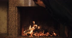 Stock Video Footage of Adult man blowing into a fireplace to cause sparkles. Slow motion 120fps. 4k