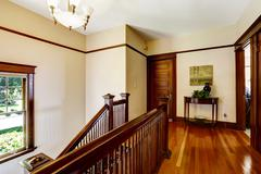upstairs hallway with hardwood floor and staircase - stock photo
