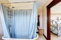 bathroom with bath tub and blue curtain around it - stock photo