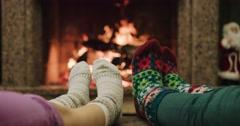 Feet in woolen socks warming by cozy fire in Christmas time in slow motion. Stock Footage