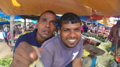 Two young salesmen chatting and smiling at the Sunday market. Stock Footage