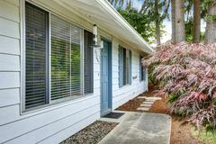 house exterior with blue trim.. entrance door and concrete walkway - stock photo