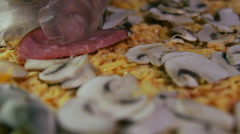 Pizzaiolo pouring salami on pizza Stock Footage