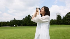 Young Japanese woman walking with vintage camera in a park Stock Footage