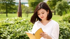 Young Japanese woman reading a book in a park Stock Footage