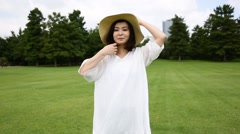 Young Japanese woman with straw hat walking in a park Stock Footage