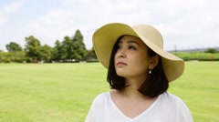 Young Japanese woman with straw hat in a park Stock Footage
