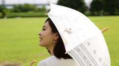Young Japanese woman walking with parasol in a park Stock Footage
