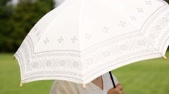Young Japanese woman with parasol in a park Stock Footage
