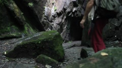 Man enters mountain cave Stock Footage