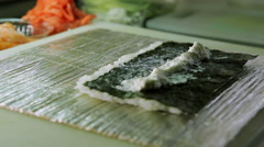 Chef spreading cream cheese and puts salmon while cooking sushi rolls Stock Footage