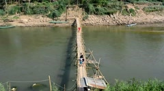 People walk on a bamboo bridge on the Nam Khan River, Luang Prabang ,Laos Stock Footage