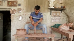 Man Sits At Pottery Wheel In Open Air. Making Pottery - stock footage