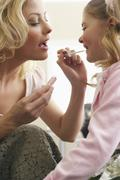 Mother Applying Lipgloss to Daughter Stock Photos