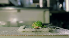 Rolling up the sushi roll with bamboo mat, close up view Stock Footage