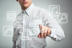 Young businessman pressing application button on computer with touch screen Kuvituskuvat