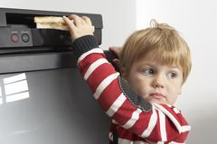 Boy Putting Sandwich in VCR Stock Photos