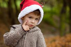 Sad little boy in the park, with santa hat, showing his hurt cheek from a fal Stock Photos