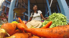 Portrait of smiling woman selling her fresh vegetables on market. - stock footage