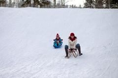 Boy and mom, sitting on a sledge, going down on the hill Stock Photos