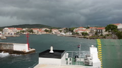 Ferry leaves small village port Stock Footage