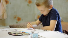 little beautiful boy draws in the room - stock footage