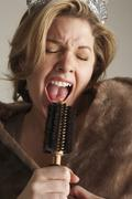 Woman Dressed Up, Singing Into Hair Brush Stock Photos
