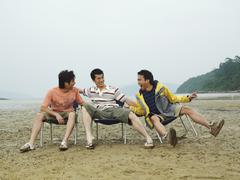 Men Goofing Around on the Beach - stock photo