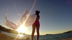 Slow motion of silhouette of dancing woman sith scarf on the beach wind, insp Stock Footage