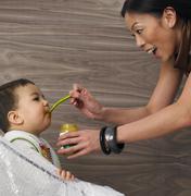 Mother Feeding Son Stock Photos