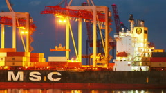 Unloading container cargo freight ship in container terminal in night time Stock Footage
