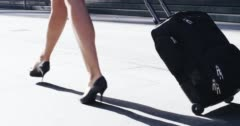 Sexy business woman traveler carry on luggage airport travel concept Stock Footage