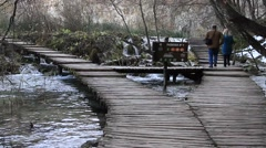 Couple walking on wooden bridge at Plitvice lakes national park  Stock Footage