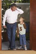 Father and Son Arriving Home Together Stock Photos