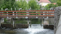 Historical weir flowing through cityscape Stock Footage