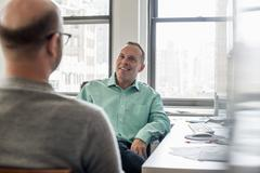 Two men seated in a light airy office environment, talking. Stock Photos