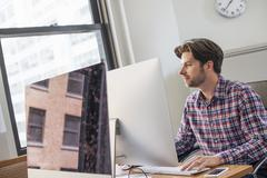 A man in achecked shirt sitting at an office desk using a computer. Stock Photos