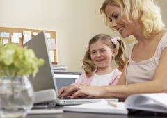 Mother Using Lap Top with Daughter Kuvituskuvat