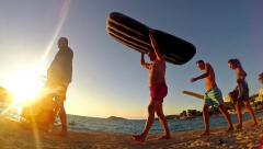 summer concept. silhouette tourists walking with beach accessories at sunset - stock footage