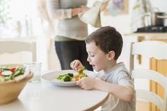 Stock Photo of boy (6-7) eating healthy dinner, mother in background