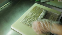 Rolling up the sushi roll with bamboo mat, upside view Stock Footage